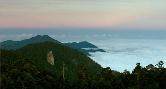 在落日餘暉中,以獨特的光潔之姿聳立於層巒疊翠中的Pusu Qhuni,翻過山嶺是雲海繚繞的藍山。這是賽德克族傳說中的祖源地──半岩半木的巨石,一般稱為牡丹岩。(紀錄片《餘生》的鏡頭截圖,導演湯湘竹先生提供)